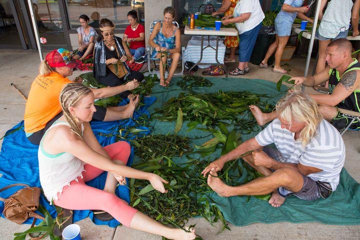 Volunteers weave the mile-long lei for Paris.