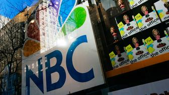 NEW YORK - DECEMBER 03:  An NBC store is seen through a window reflecting Rockefeller Center, headquarters of General Electric, owner of NBC Universal, December 3, 2009 in New York City.  Comcast Corporation announced December 3 that it plans to buy a majority stake in NBC Universal for $13.75 billion in cash and assets.   (Photo by Chris Hondros/Getty Images)