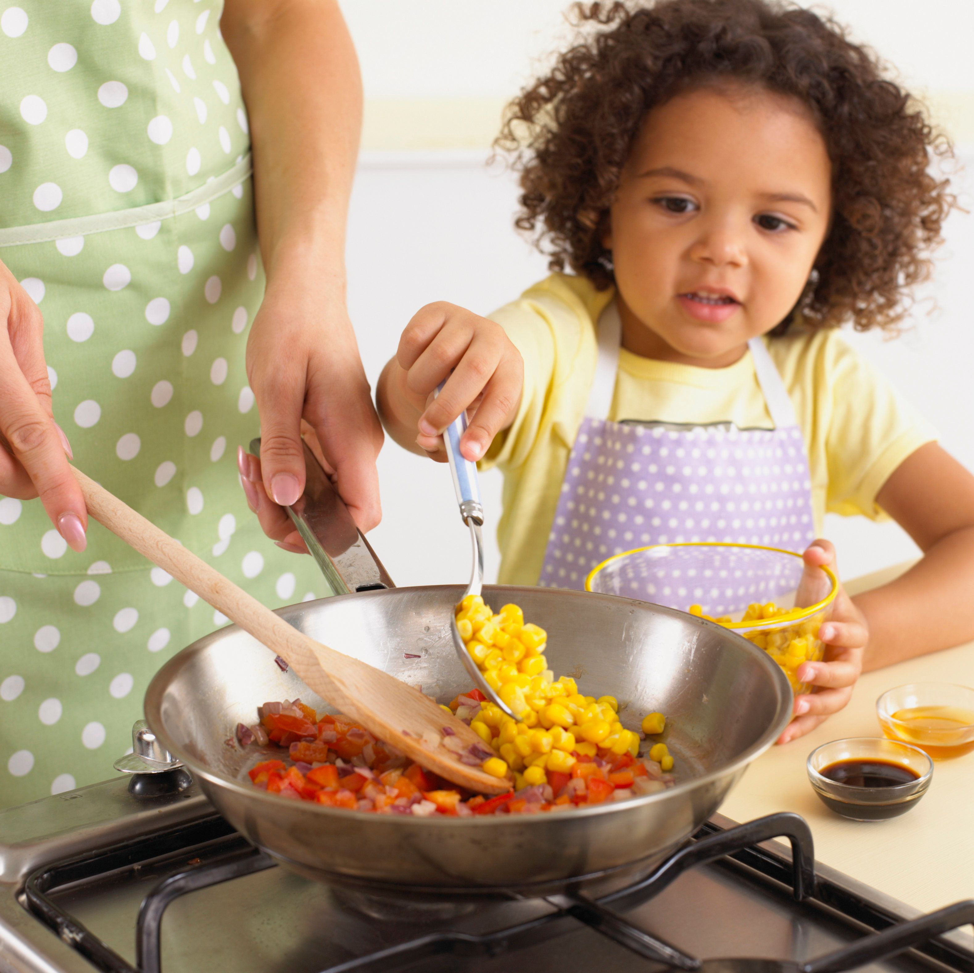 Girl adding sweetcorn with spoon, alongside woman stirring onions and red bell peppers in frying pan, bowls of sweetcorn, vinegar and honey on kitchen worktop, close-up