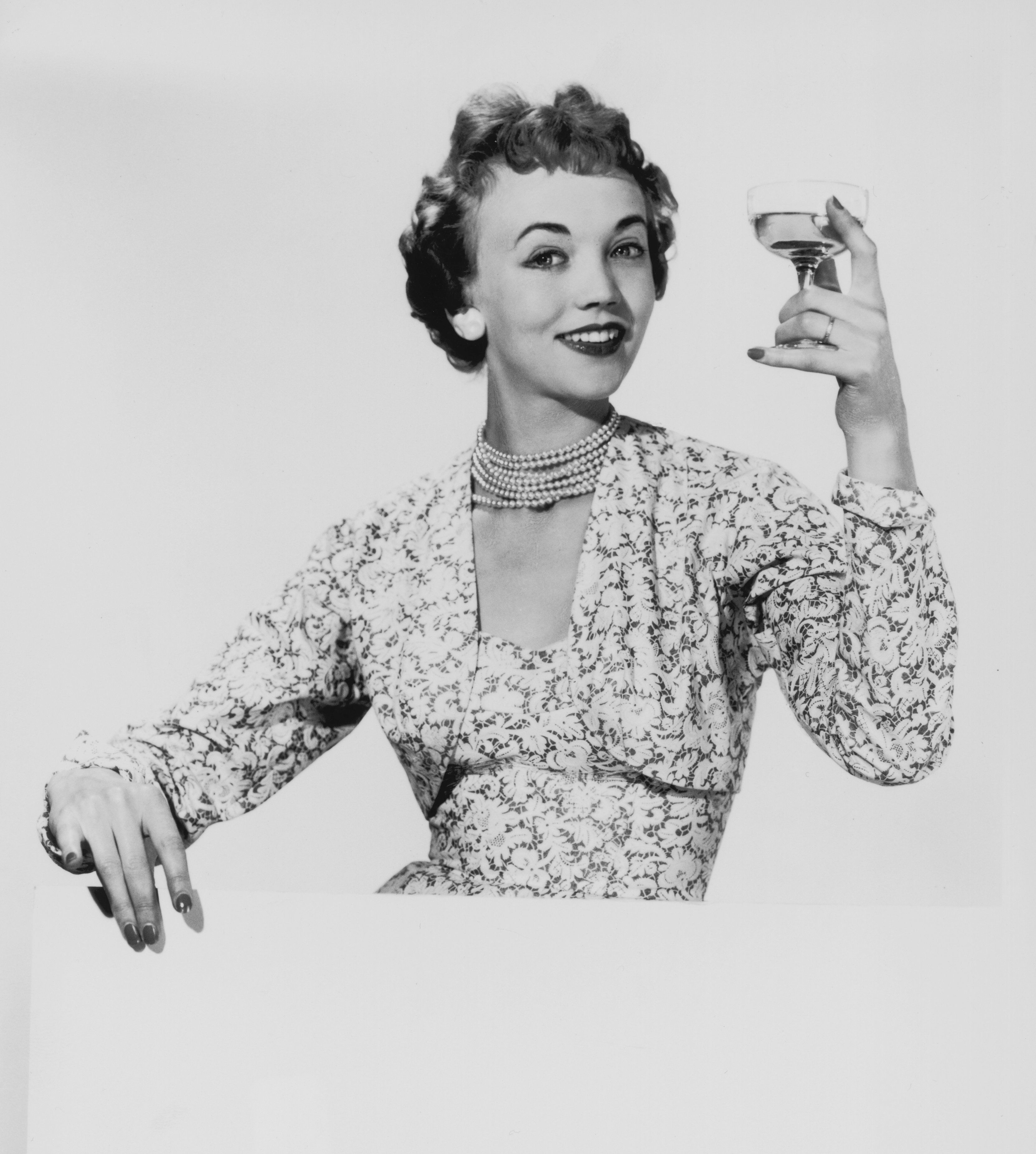 1955:  A woman in a matching dress and bolero proposes a toast.  (Photo by Chaloner Woods/Getty Images)