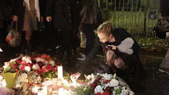 BATACLAN THEATRE, PARIS, ÎLE-DE-FRANCE, FRANCE - 2015/11/17: A woman places a candle at the memorial opposite the Bataclan Theatre, the place, where the most people of the Paris attacks died. Parisians and tourists continue to visit the memorials for the people killed in the terrorists attacks in Paris, to lay down flowers and candles and to pay their respect. Over 130 people have been by terrorist from the Islamic State. (Photo by Michael Debets/Pacific Press/LightRocket via Getty Images)