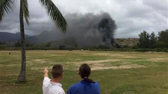 In this May 17, 2015, file photo, a man and woman look toward smoke rising from a Marine Corps Osprey aircraft after it made a hard landing at Bellows Air Force Station near Waimanalo, Hawaii. A military investigation says the hybrid aircraft crashed when its left engine stalled after flying in sandy or dusty conditions for an extended period. (Zane Dulin via AP)