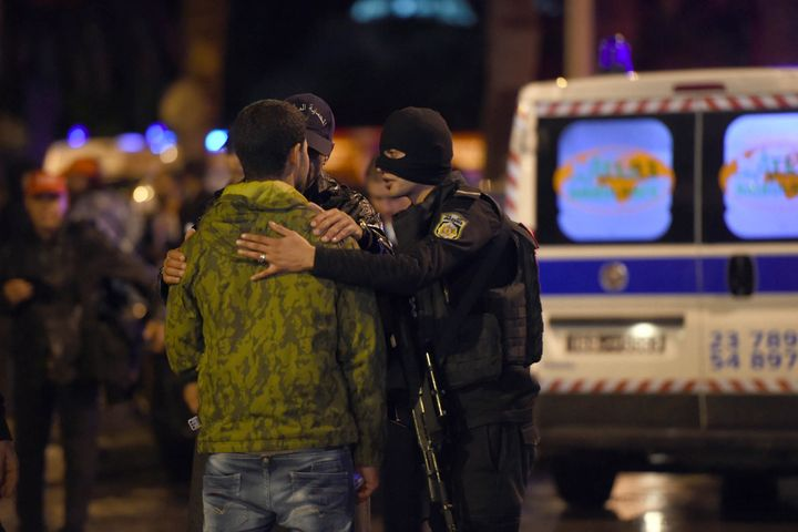 Tunisian police console a family member of one of the victims of theblast. At least 12 people were killed.