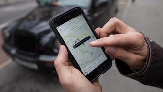 A user scans for an available vehicle using the Uber Technologies Inc.'s app on an Apple Inc. iPhone 6 smartphone in this arranged photograph in London, U.K., on Thursday, May 14, 2015. Data obtained by Bloomberg from Transport for London, the transit authority, show black-taxi license applications are down 20 percent so far this year, with the blame being laid squarely at Uber Technologies Inc.'s door. Photographer: Simon Dawson/Bloomberg via Getty Images
