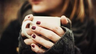 A woman holding a hot drink in gloved hands.