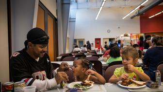 CAMDEN, NJ - AUGUST 21:  LeManuel Farrish helps his cousin, Makayla Farrish, age three, finish her dinner at Catherdral Kitchen on August 21, 2013 in Camden, New Jersey. Cathedral Kitchen is a mutli-service soup kitchen that has been serving the Camden homeless community since 1976. They serve between 300 and 600 dinners each night, as well as offering bi-weekly dental services, and periodic medical and legal services as well.  (Photo by Andrew Burton/Getty Images)