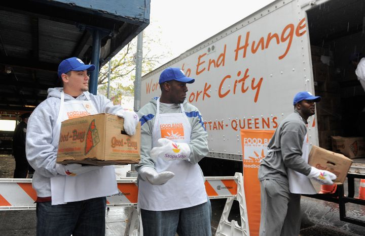 NEW YORK, NY - NOVEMBER 22: (L-R) New York Giants Team members Jim Cordle, Kevin Boothe and Chris Canty off load turkeys' as