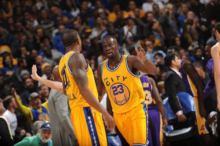 Golden State Warriors' Draymond Green, right, high-fives teammate Andre Iguodala during the spectacular performance.
