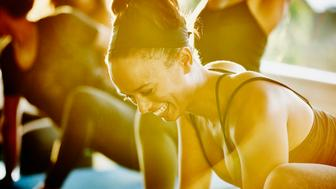 Smiling woman laughing with friends during yoga class in studio