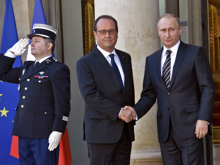French President Francois Hollande (L) shakes hands with Russian President Vladimir Putin upon his arrival at the Elysee Pala