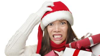 Christmas stress - busy xwoman wearing santa hat stressing for christmas shopping holding may christmas gifts in her arms. Funny image of multiracial Asian Caucasian female model isolated on white background. More: