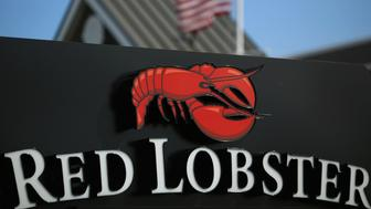 An American flag flies past Red Lobster signage displayed outside of a restaurant location in Clarksville, Indiana, U.S., on Monday, June 22, 2015. Red Lobster is a casual dining restaurant chain that is headquartered in Orlando, Florida. Photographer: Luke Sharrett/Bloomberg via Getty Images
