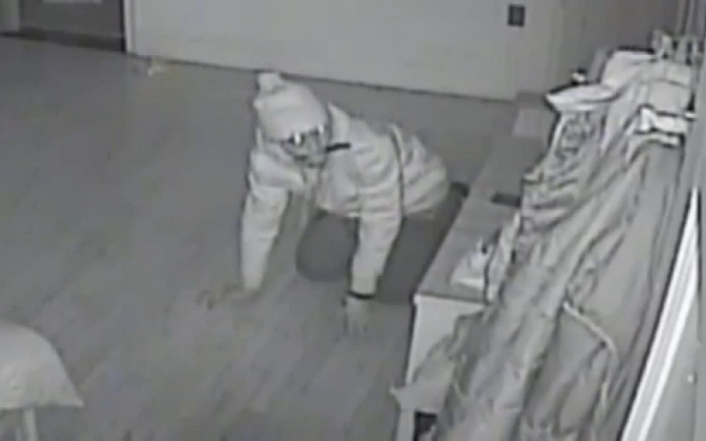 Video captured the brazen burglar crawling around the sleeping family's beds with a knife in his mouth.