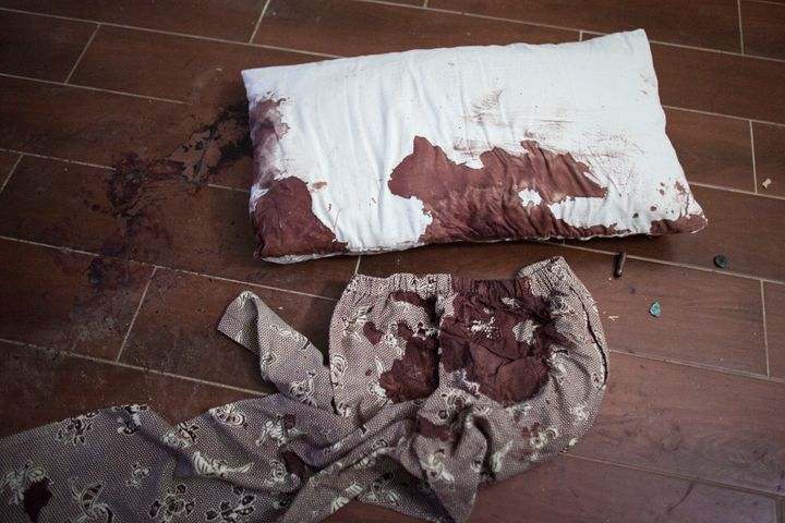 A blood stained pillow and pants lie on the floor next to bullet casings in a guest room of the Radisson Blu Hotel.