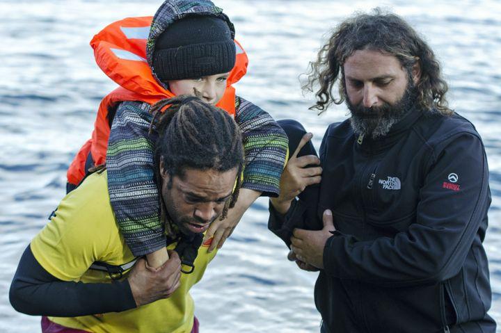Volunteers help refugees arriving in Lesbos on Nov. 26, 2015.