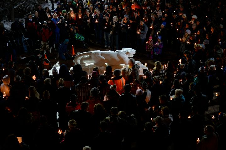 Hundreds gather around the University of Colorado at Colorado Springs Mountain Lion statue during a candlelight vigil at the