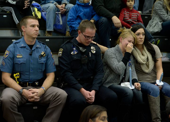 University of Colorado Colorado Springs police officer Jerod Heidrick, second from left, takes a moment as his friend Courtne