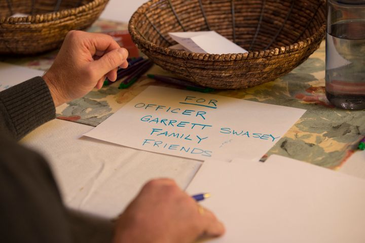 People write notes for Officer Garrett Swasey family and friends and Planned Parenthood before a vigil at the All Souls Unita