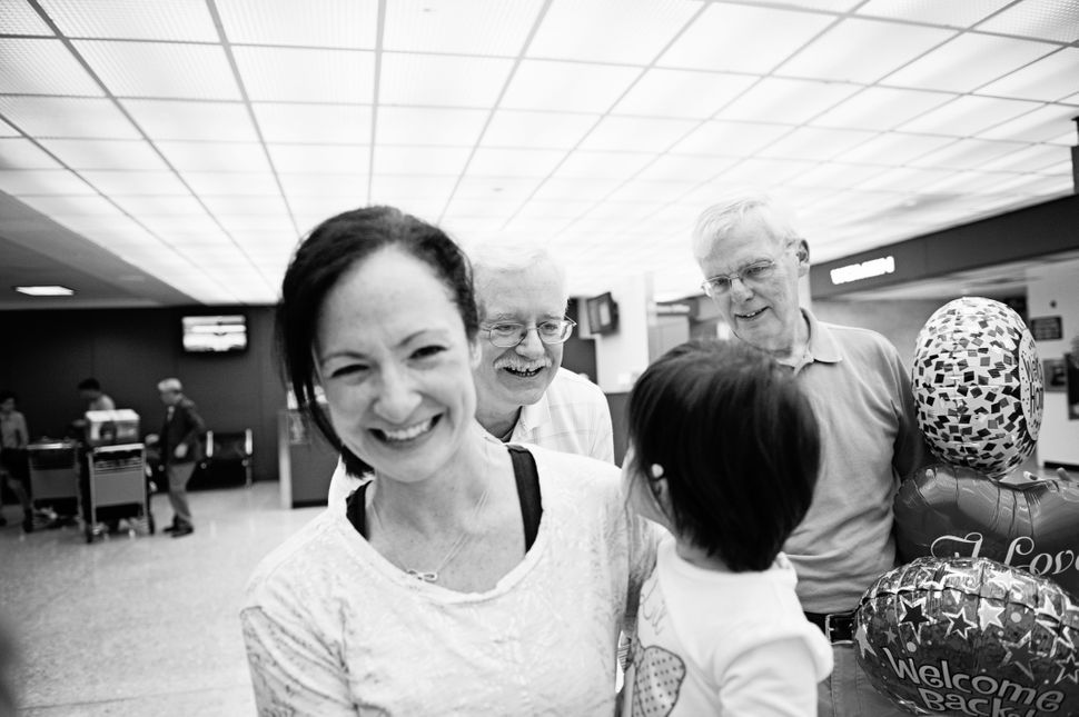 <i>Olivia came home to her family Steve, Kristen and Ryan in Virginia.Her grandfathers met her at the airport. Photo by