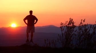 Vermont, Plainfield, Watching the sun set over the mountains for which this state is named. Atop Bald Hill a man watches the sun sink behind the Green Mountains.