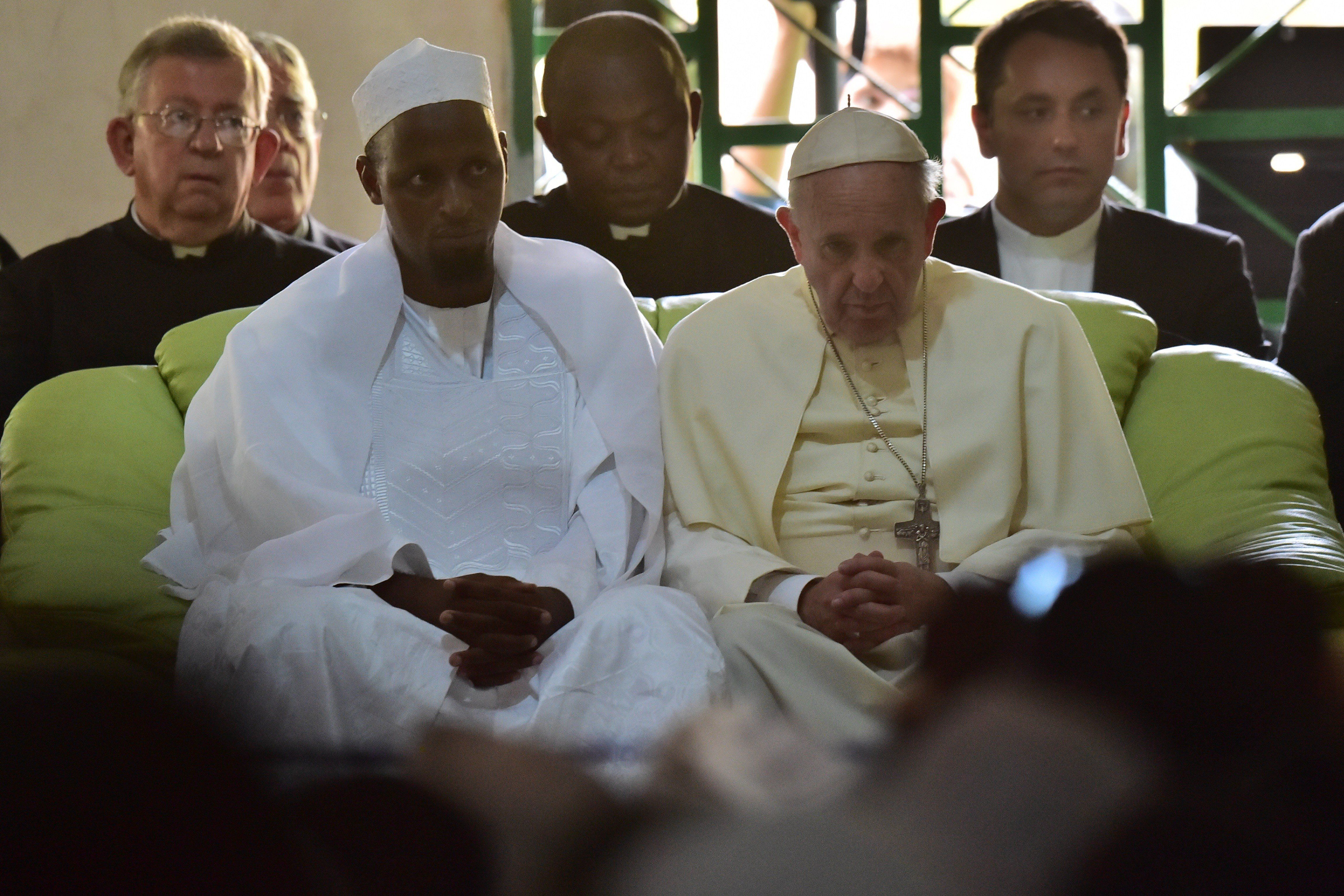 Pope Francis (C) looks on, alongside Imam Nehedid Tidjani (2-L), during a visit to the Central Mosque in Bangui on November 3