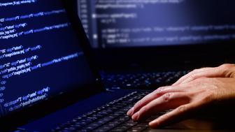 hacker using laptop. lots of...