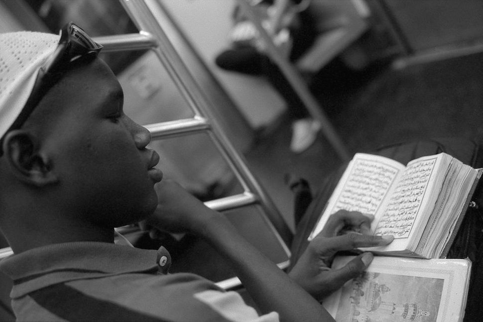 Young Man Studying the Koran on the Uptown 6 Train, Manhattan, NY 2014