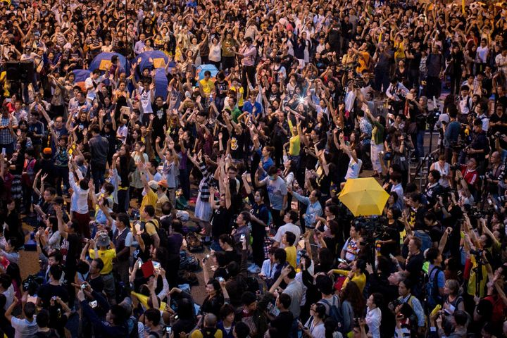 Pro-democracy activists hold up umbrellas and sing songs on a street outside Hong Kong's Government Complex in October 2014.&