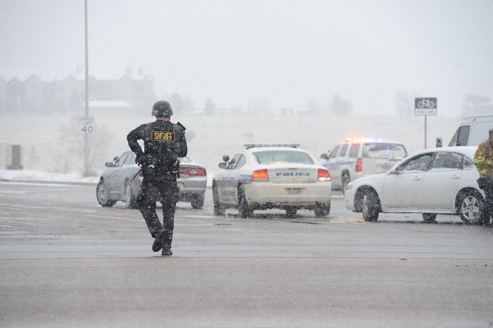 COLORADO SPRINGS, CO - NOVEMBER 27: An officer patrols the perimeter during a shooting incident in Colorado Springs, CO.