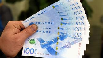 YINCHUAN, CHINA - NOVEMBER 26: (CHINA OUT) A citizen shows the 100-yuan (about 15.65 USD) aerospace commemorative bank notes issued by The People's Bank of China on November 25, 2015 in Yinchuan, Ningxia Hui Autonomous Region of China. The People's Bank of China (PBOC), the country's central bank, issued 300 million aerospace commemorative 100-yuan bank notes and 100 million aerospace commemorative 10-yuan coins on Thursday.  (Photo by ChinaFotoPress/ChinaFotoPress via Getty Images)