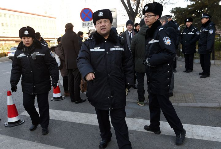 Chinese police stand guard outside the Beijing City High Court earlier this month.