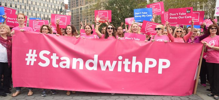 Activists in New York City hold a Planned Parenthood banner to demonstrate their support for the organization.