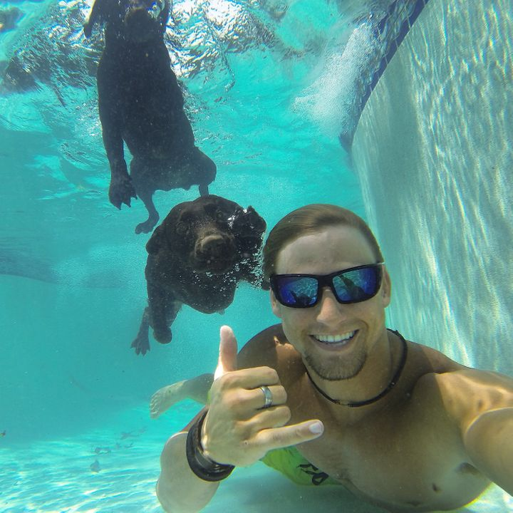 Alex Schulze poses underwater with Maverick and Lila.