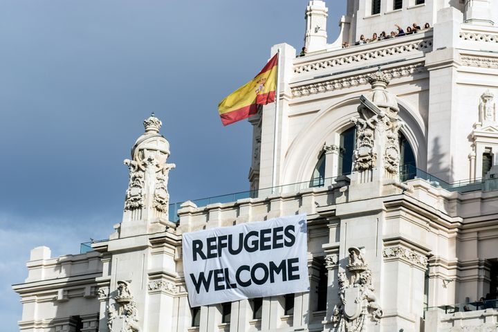 A view of Madrid City Hall with a banner that welcomes refugees.