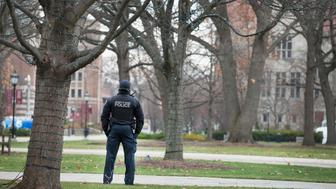CHICAGO, IL - NOVEMBER 30:  A police officer stands watch in the Main Quadrangles (Quad) on the Hyde Park Campus of the University of Chicago on November 30, 2015 in Chicago, Illinois. The university president closed the campus today after the university was informed by the FBI that a threat of gun violence was made against the school specifically mentioning the 'campus quad'.  (Photo by Scott Olson/Getty Images)