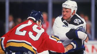 Canadian hockey player Rudy Poeschek of the Tampa Bay Lightning fights a Florida Panther during a game, 1990s. (Photo by Bruce Bennett Studios/Getty Images)