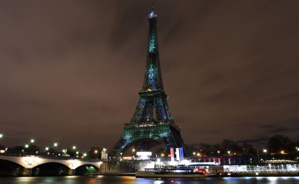 A picture taken on November 30, 2015 shows the Eiffel Tower lit up with green color and messages to prevent global warming du