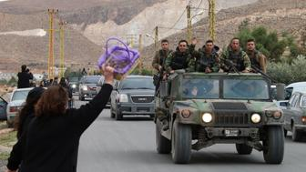 A woman gestures to a convoy of the Lebanese army in the village of Labweh in the Bekaa Valley on December 1, 2015, as Lebanese soldiers and policemen kidnapped by jihadist groups from the eastern border town of Arsal last year are being released. Al-Qaeda's Syrian affiliate freed 16 Lebanese soldiers and police it had held for more than a year in exchange for the release of prisoners and delivery of aid. AFP PHOTO / STR / AFP / -        (Photo credit should read -/AFP/Getty Images)