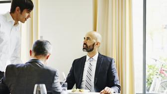 Two businessmen sitting at table in restaurant in discussion with server