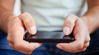 Hands of a casual man using a smartphone.