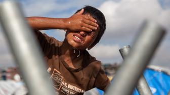 KATHMANDU, NEPAL - AUGUST 13: A young boy washes his face at one of the water taps set up inside the Chuchepati displacement camp on August 13, 2015 in Kathmandu, Nepal. About 7,144 people, hailing from different affected districts by the earthquake that hit Nepal, currently live in Chuchepati camp, with access to only 35 toilets and the help of only a few NGOs. Approximately 60,000 people are still living in over 100 official displacement camps throughout the affected districts. Living conditions in the camps are dire, with limited or non-existent access to sanitation services, clean water and food, and health services. These conditions have been made worse by heavy monsoon rains, as the camps most often lack drainage systems and are prone to flooding. (Photo by Omar Havana/Getty Images)