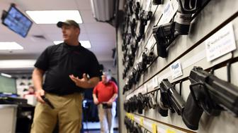 Paul Bastean, owner of the Ultimate Defense Firing Range and Training Center in St Peters, Missouri, some 20 miles (32 kilometers) west of Ferguson, arranges a rack of handguns on November 26, 2014. Bastean told AFP that business had grown as a result of anxiety about reaction to the jury announcement in the shooting death of 18-year-old Michael Brown. Typical sales of five to seven guns a day have risen to 20 to 30 in the last week, while gun-handling courses for November and December are fast selling out. Violence erupted in the St Louis, Missouri suburb for a second night on November 25 over the decision by a grand jury not to prosecute a white police officer for shooting dead Brown, an unarmed black teenager. AFP PHOTO/Jewel Samad        (Photo credit should read JEWEL SAMAD/AFP/Getty Images)