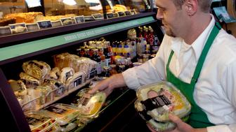 DENVER, COLO. - JULY 7, 2004 - Starbucks Partner <cq> Adam Greener <cq> tidies up a refrigerated case of sandwiches, salads and cold bottles drinks at the Starbucks at 16th and Blake in downtown Denver. Starbucks began selling prepackaged sandwiches and salads at half of its 118 Colorado stores Wednesday, 7/7/04. (Jerry Cleveland / The Denver Post)  (Photo By Jerry Cleveland/The Denver Post via Getty Images)