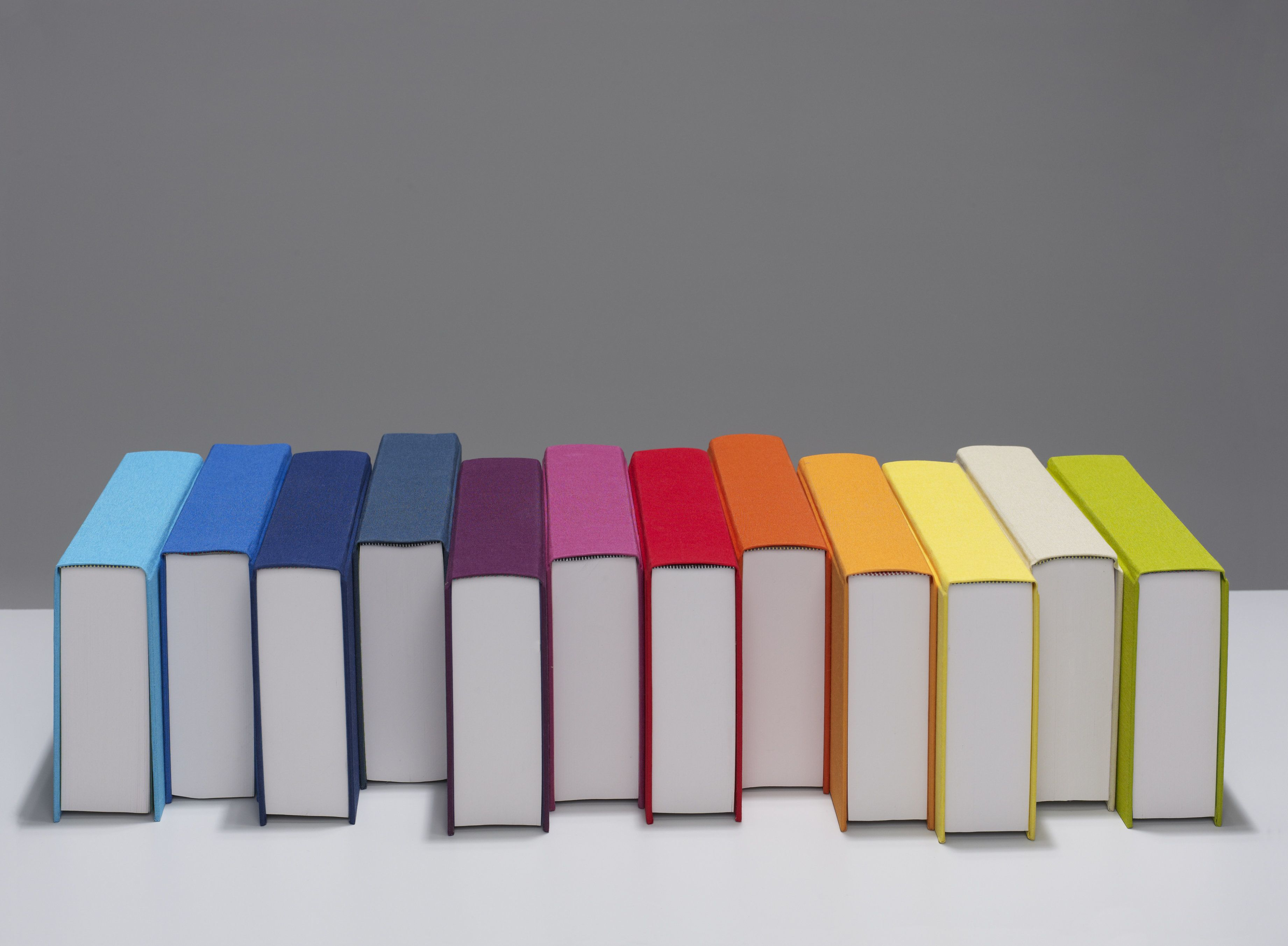 coloured books lined up in rainbow spectrum on desk
