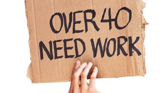Subject: Unemployment for middle age workers, a hand holding up cardboard sign with 'OVER 40 NEED WORK' written.
