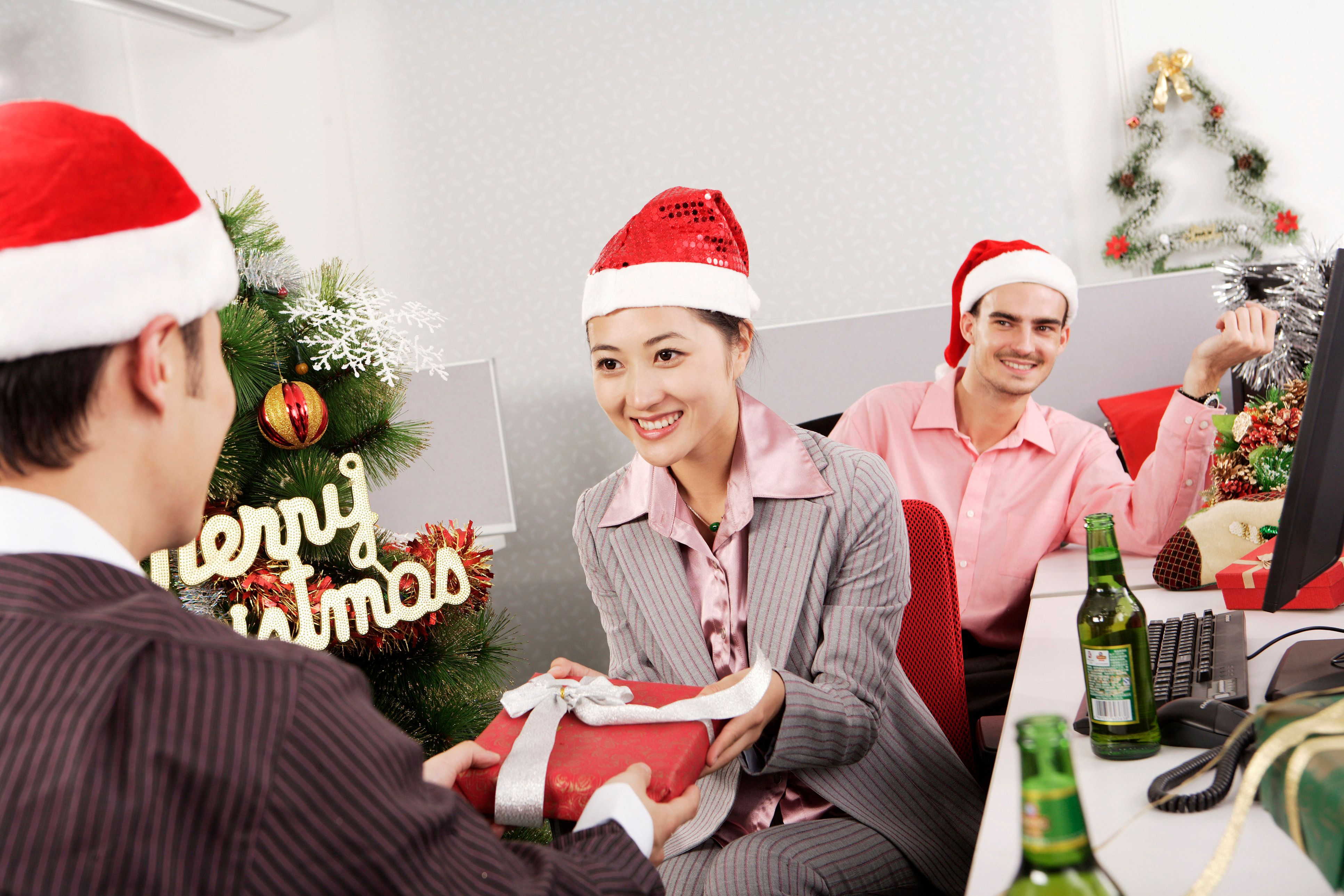 Office woman giving gift to man on Christmas Day