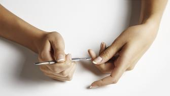 Close up of woman's hands removing cuticle with metal stick