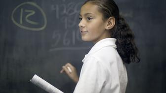 Ten year old Hispanic girl solves math problem in classroom.