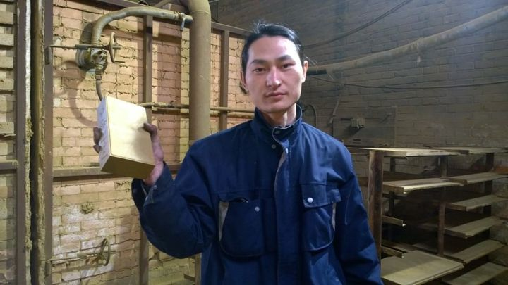 "Wang holds his pollution brick. ""I want to show this absurdity to more people,"" he said."