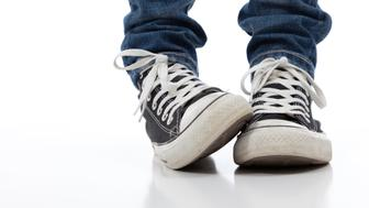 A pair of vintage looking athletic shoes and blue jeans on a white bakcground.  Signifying shyness or nervsousness